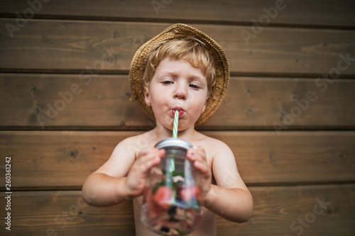 Vászonkép A small boy with a drink standing against wooden background on a patio in summer