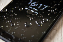 Front Side Of Waterproof Smartphone Covered With Drops Of Water
