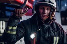 Portrait Of A Handsome Fireman Wearing A Protective Uniform With Flashlight Included Standing In A Fire Station Garage