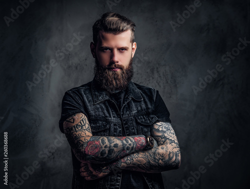 Portrait of a stylish bearded guy with tattooed hands. Studio photo against dark wall Wall mural