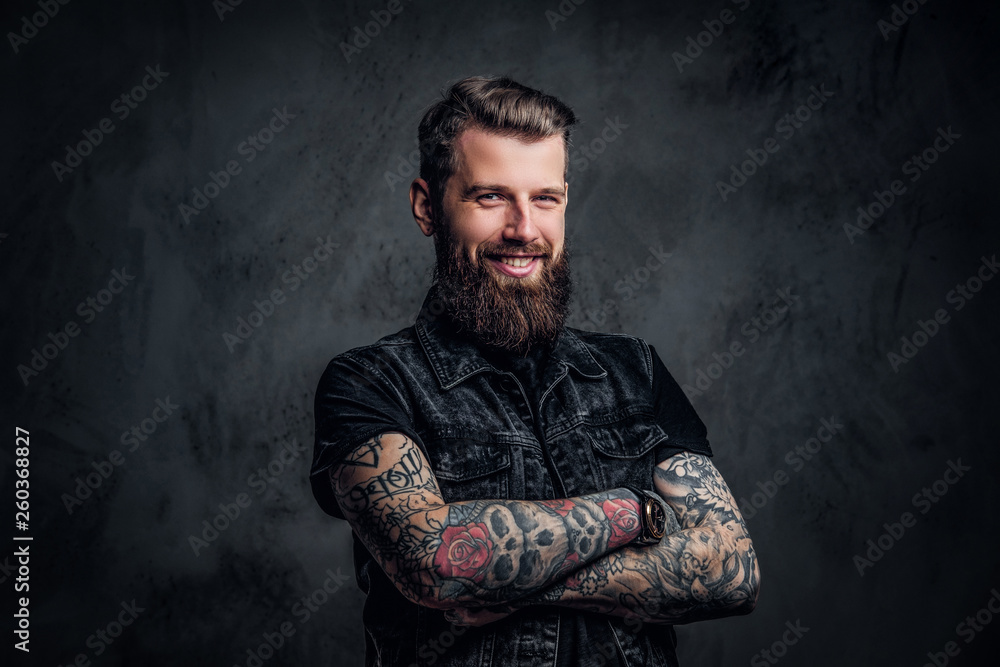 Fototapeta Portrait of a stylish bearded guy with tattooed hands. Studio photo against dark wall