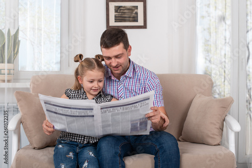Valokuva  Little daughter and dad sitting on the sofa at home and reading the newspaper to