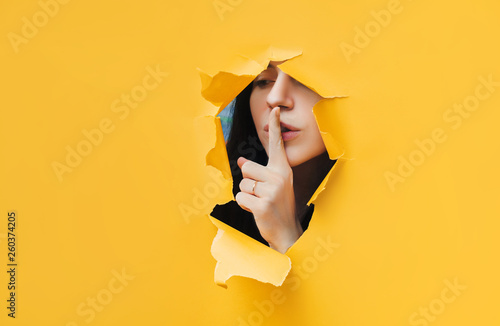 Photo  A young girl closes her lips with her index finger,making it clear to the viewer that you need to observe silence,keep a secret and not say too much