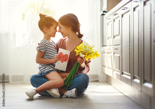 happy mother's day! child daughter   gives mother a bouquet of flowers to narcissus and gift. - 260376068