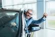 businessman sitting in car and showing car keys in car dealership showroom