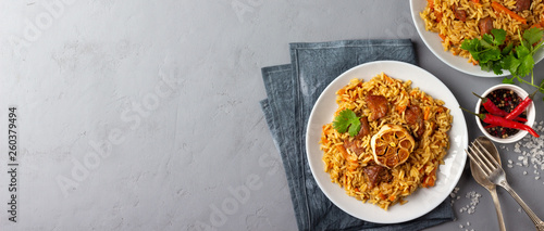 Fotografie, Obraz  Traditional asian dish - pilaf from from rice, vegetables and meat in a plate on gray background