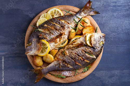 Obraz na plátně Grilled fish with roasted potatoes, lemon and rosemary on wooden tray