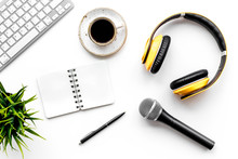 Blogger Work Space With Microphone, Notebook, Keyboard And Headphones On White Background Top View Space For Text