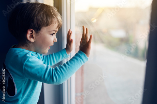 Fotografia, Obraz  Little boy at home looking trough the window at his friends playing in the yard