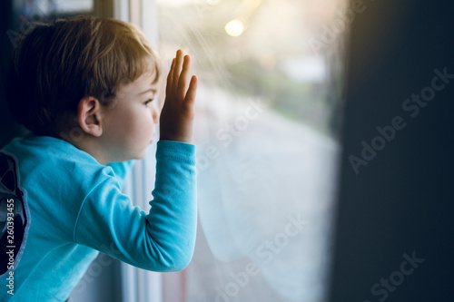 Valokuva Little boy at home looking trough the window waiting for his mother to come back