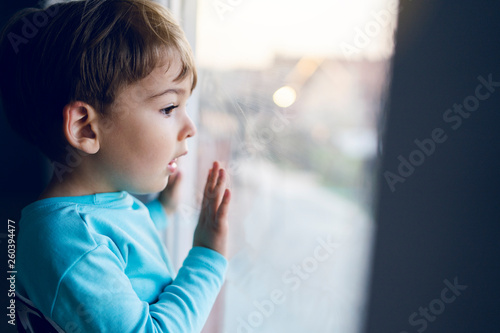 Fotografie, Obraz Little boy at home looking trough the window waiting for his mother parents to c