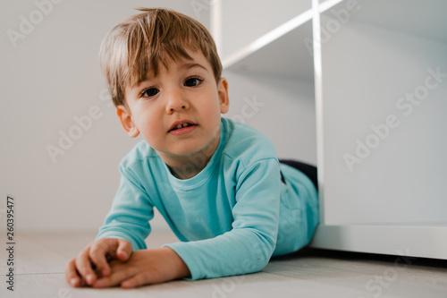 Fototapeta Portrait of a little boy in blue at home lying in the book shelf on the floor hi