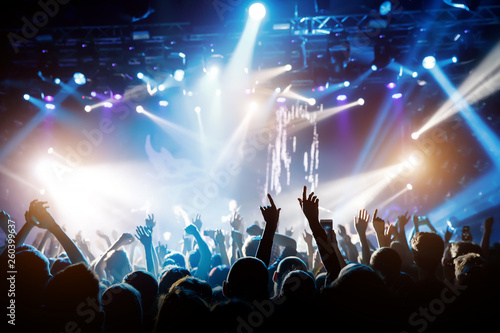 Concert hall with a lit stage and people silhouettes during a concert - 260399637