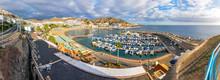 Panoramic Aerial View Of Sea Port And Small Bay Of Puerto Rico De Gran Canaria Holiday Resort. Gran Canaria Island, Spain