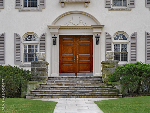 Stucco House With Elegant Double Wooden Front Door And Stone