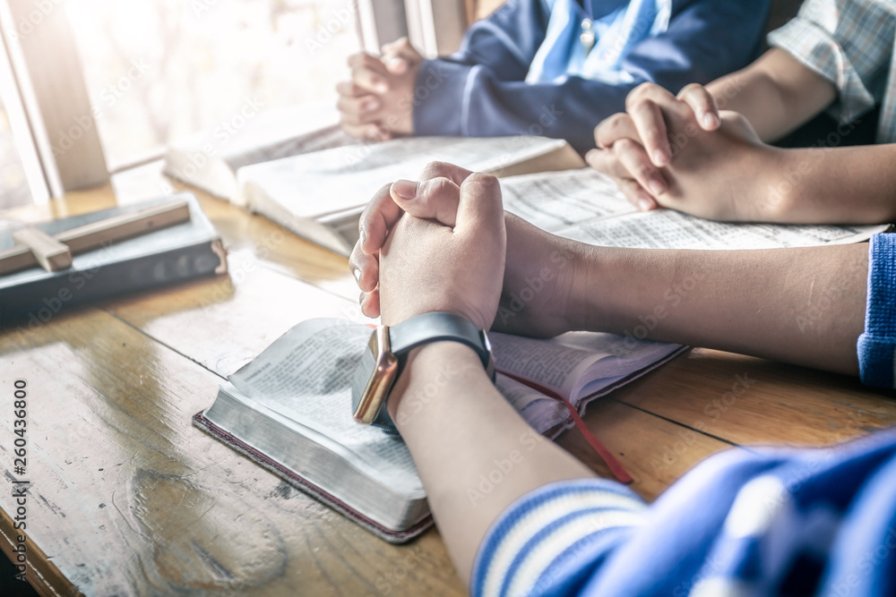 Fototapety, obrazy: Christian children group praying on wooden table with open bible page at home, prayer meeting concept.