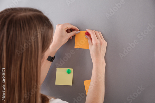 Woman attaching papers to fridge door Canvas Print