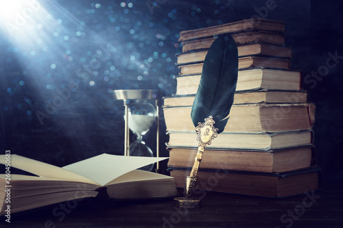 Fotografie, Obraz Old feather quill ink pen with inkwell and old books over wooden desk in front of black wall background
