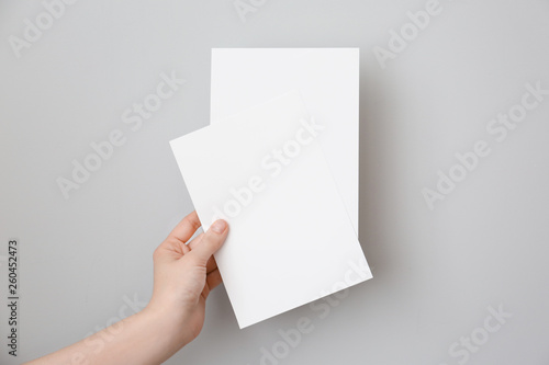 Fotografia, Obraz  Female hand with blank invitation cards on light background