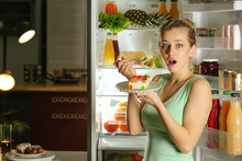Afraid Woman Caught In The Act Of Eating Tasty Unhealthy Food Near Refrigerator At Night