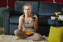 Beautiful Young Woman Eating Unhealthy Food While Watching TV At Night