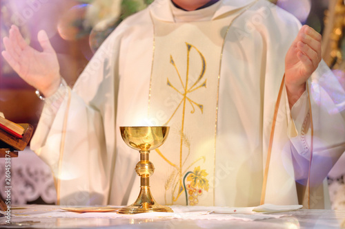 Fotografia Chalice at the altar with rays of light and Priest celebrate mass
