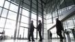 4K Businessmen meet & shake hands in busy modern office building