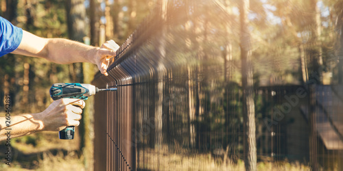 Fotografia, Obraz fencing - worker installing metal wire mesh fence panel