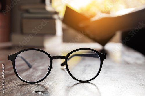 Fotografía  focus at glasses and background of woman sitting in a cafe, reading book