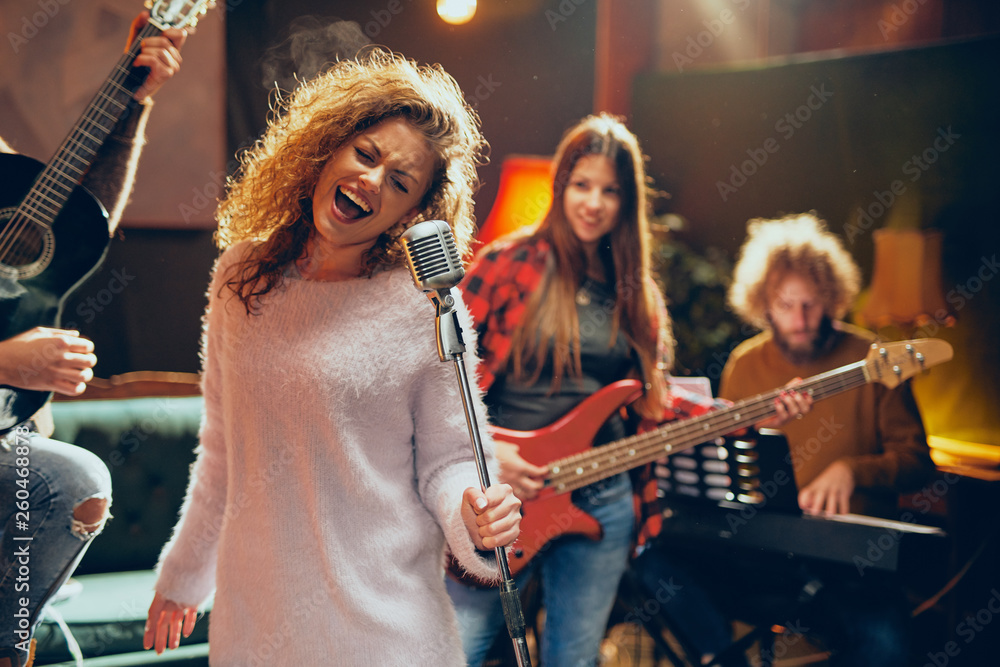Fototapety, obrazy: Band practice for the show. Woman with curly hair holding microphone and singing while man in background playing acoustic guitar. Home studio interior.