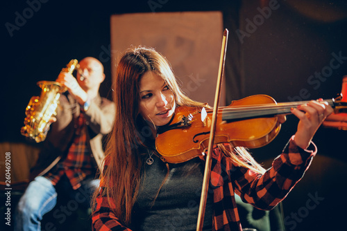 Two talented musicians playing violin and saxophone. Home studio interior. - 260469208