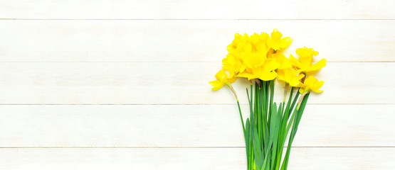 Spring floral background. Yellow narcissus or daffodil flowers on white wooden background top view flat lay. Easter concept, International Women's Day, March 8, holiday. Card with flowers copy space
