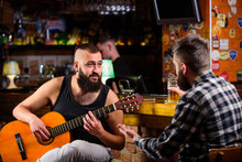 Hipster Brutal Bearded Spend Leisure With Friend In Bar. Real Men Leisure. Cheerful Friends Relax With Guitar Music. Man Play Guitar In Bar. Friday Relaxation In Bar. Friends Relaxing In Bar Or Pub