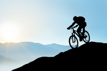 Silhouette Of Cyclist Riding The Bike Down The Rock At Sunrise. Extreme Sport And Enduro Biking Concept.