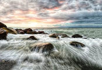 FototapetaWaves are breaking through rocks in this ocean seascape sunset.