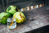 Fresh coconut juice in the jar and ripe coconuts on the vintage wooden table. - 260500069