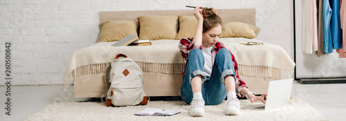Teenager with laptop sitting on carpet and doing homework