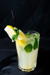 A glass with classic iced lemonade with lemon slice and leaves of mint on dark background