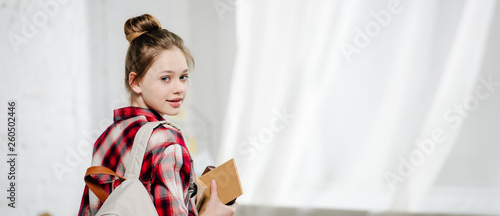 Panoramic shot of teenager with backpack holding books and looking at camera Fototapeta