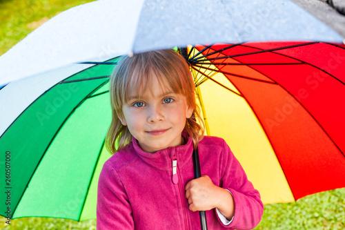 Obraz na plátne Little girl standing under umbrella in a rain outdoors