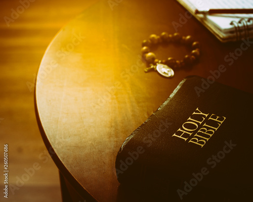 Holy Bible, rosary bracelet and notepad on desk with light flare. Bible study concept.