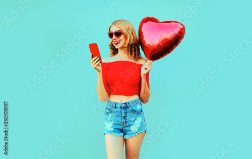 Photo  Portrait pretty happy smiling woman holding phone, red heart shaped air balloon