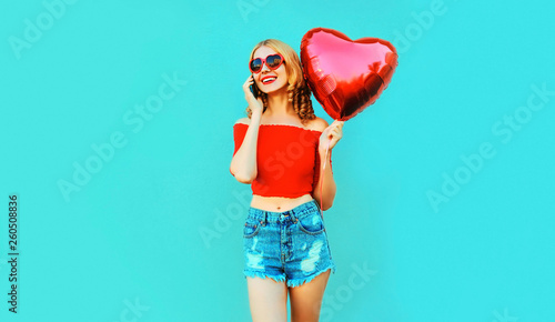 Portrait happy smiling woman calling on smartphone holding red heart shaped air Poster Mural XXL