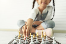 Happy Asian Girl Playing Chess At Home.