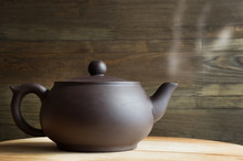 Large Hot Chocolate Clay Teapot With Steam On Wooden Background. Front View. Copy Space, Space For Text.