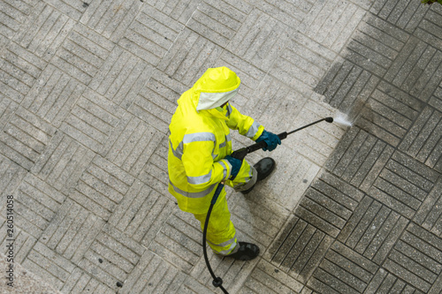 Carta da parati  Top view of a Worker cleaning the street sidewalk with high pressure water jet o