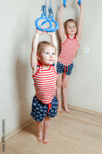 Two little girls are doing gymnastics on the rings in the children's