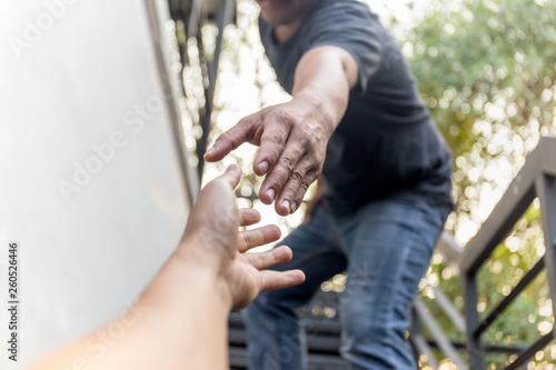 Fotografía  Help concept hands reaching out to help each other with bokeh background