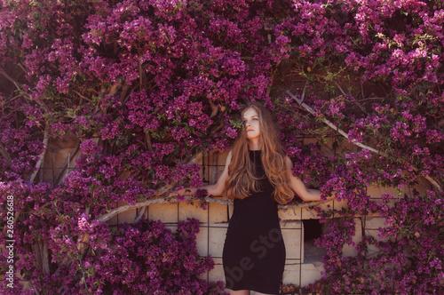 Foto Portrait of girl among purple bougainvillaea
