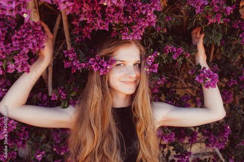 Fotografering Portrait of smiling girl among purple bougainvillaea